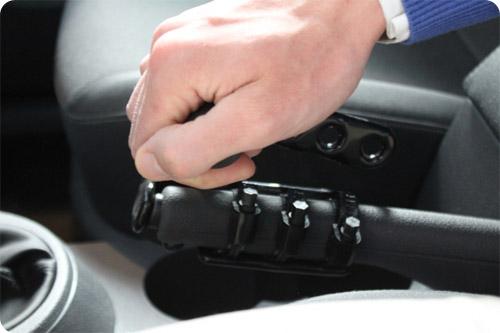En tirant vers l'arrière, la poignée appuie sur le bouton du frein à main